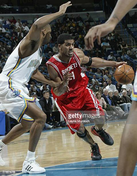 Alton Ford of the Houston Rockets drives around Steve Smith of the New Orleans Hornets on December 5 2003 at New Orleans Arena in New Orleans LA NOTE...
