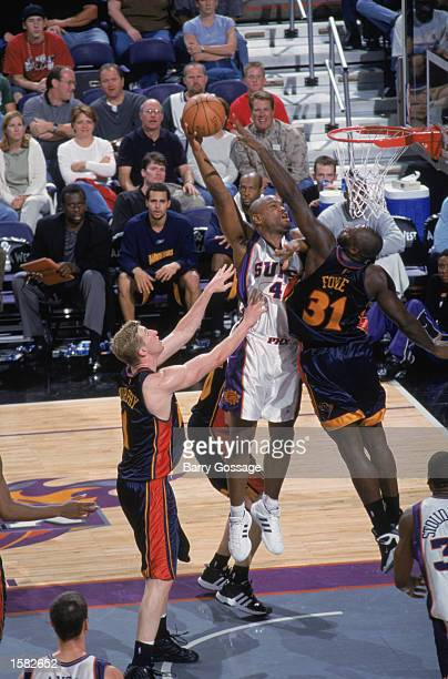 Alton Ford of the Phoenix Suns leaps for the layup over Adonal Foyle of the Golden State Warriors during the NBA preseason game at America West Arena...
