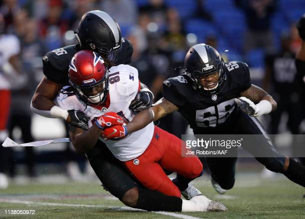 Alton Pig Howard of the Memphis Express is tackled by Beniquez Brown and Shaheed Salmon  #56 of the Birmingham Iron during the first quarter of their...