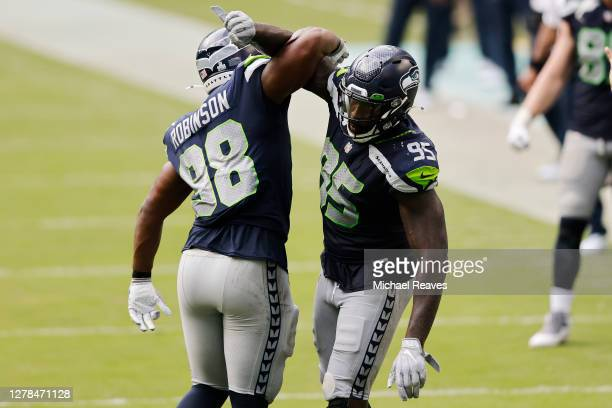 Alton Robinson and Benson Mayowa of the Seattle Seahawks celebrate against the Miami Dolphins during the second half at Hard Rock Stadium on October...