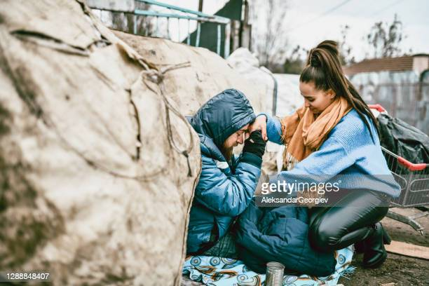 altruist female warming homeless male with jacket - selfless stock pictures, royalty-free photos & images