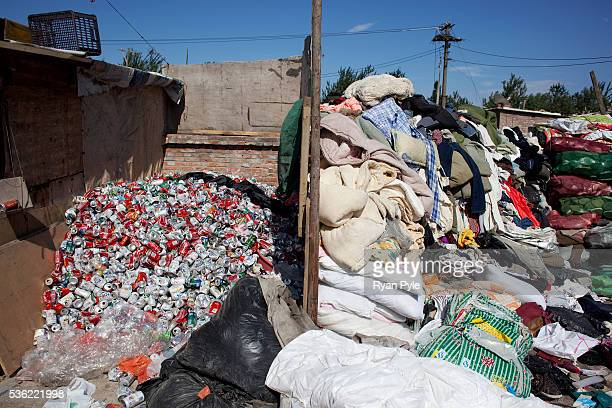 Aluminum cans are piled next to clothes and blankets in the Dongxiaokou village Dongxiaokou village is a small village just on the outskirts of...