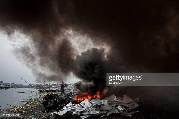Aluminum foil papers that are rejected by the small industries are burning at the bank of river Buriganga, Dhaka, Bangladesh, causing heavy air...