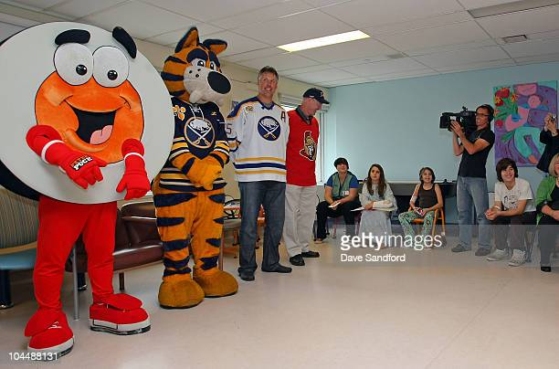 Alumni Dave Andreychuk and Brad Marsh along side Peter Puck and Buffalo Sabres mascot Sabretooth meet with patients and their families at McMaster...