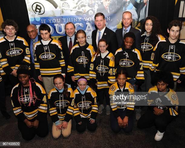 Alumni player Willi O'Ree of the Boston Bruins poses with kids of the youth hockey league SCORE Boston the NHL Commissioner Gary Bettman Boston Mayor...