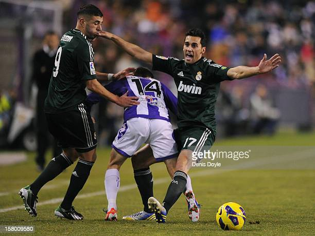 Alvaro Albeloa and Karim Benzema of Real Madrid CF battle for the ball against Julian Omar of Real Valladolid CF during the La Liga match between...