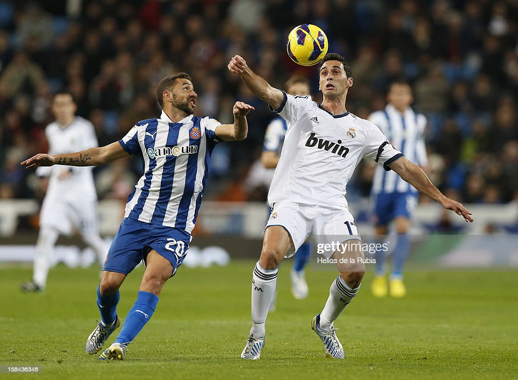 Alvaro Arbeloa (R) of Real Madrid and Simao Sabrosa competes for the ball during the La Liga match between Real Madrid and RCD Espanyol at Santiago Bernabeu stadium on December 16, 2012 in Madrid, Spain.