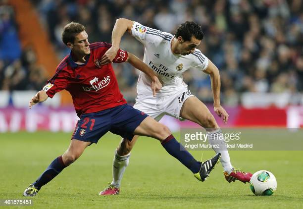 Alvaro Arbeloa of Real Madrid competes for the ball with Roberto Torres of Osasuna during the Copa del Rey round of 16 first leg match between Real...