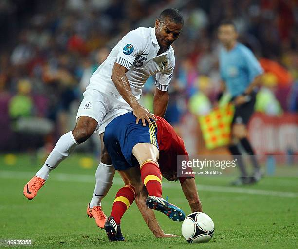 Alvaro Arbeloa of Spain and Florent Malouda of France clash during the UEFA EURO 2012 quarter final match between Spain and France at Donbass Arena...