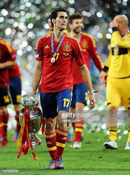 Alvaro Arbeloa of Spain walks across the picth holding the trophy following victory in the UEFA EURO 2012 final match between Spain and Italy at the...