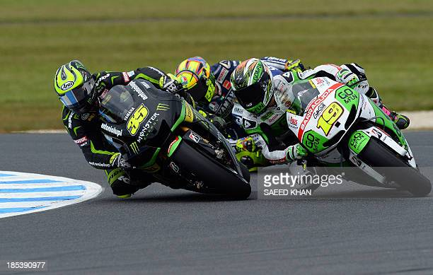 Alvaro Bautista of Spain powers his Honda next to Yamaha Tech rider Cal Crutchlow of Britain and Yamaha rider Valentino Rossi of Italy during the...