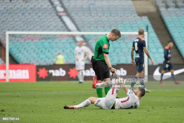 Alvaro Cejudo of the Wanderers is helped to his feet by referee Adam Fielding after being heavily tackled during the round nine ALeague match between...