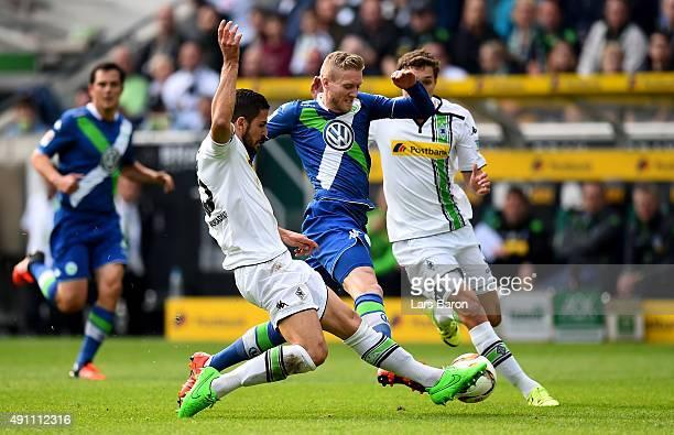 Alvaro Dominguez of Moenchengladbach challenges Andre Schuerrle of Wolfsburg during the Bundesliga match between Borussia Moenchengladbach and VfL...