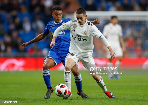 Alvaro Fidalgo of Real Madrid competes for the ball with Antonio Otegui of Melilla during the Copa del Rey fourth round second leg match between Real...