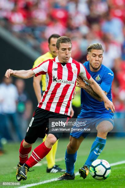 Alvaro Jimenez of Getafe CF competes for the ball with Iker Muniain of Athletic Club during the La Liga match between Athletic Club and Getafe at at...