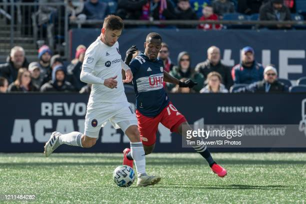 Alvaro Medran of Chicago Fire passes the ball under pressure from Cristian Penilla of New England Revolution during a game between Chicago Fire and...