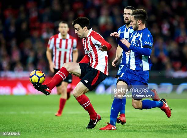 Alvaro Medran of Deportivo Alaves competes for the ball with Benat Etxebarria of Athletic Club during the La Liga match between Athletic Club Bilbao...