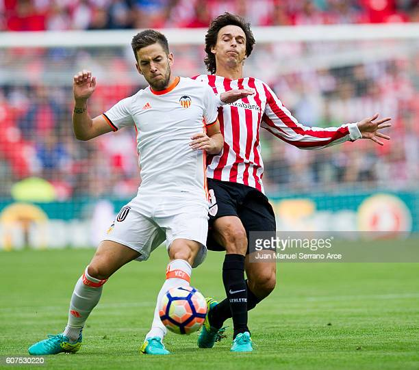 Alvaro Medran of Valencia CF competes for the ball with Ander Iturraspe of Athletic Club during the La Liga match between Athletic Club Bilbao and...