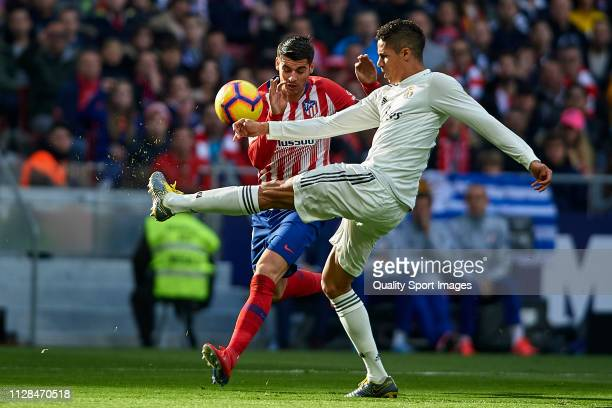 Alvaro Morata of Atletico de Madrid competes for the ball with Raphael Varane of Real Madrid during the La Liga match between Club Atletico de Madrid...