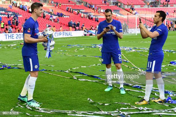 Alvaro Morata of Chelsea poses with the Emirates FA Cup trophy whilst Davide Zappacosta and Pedro of Chelsea take photos following their victory...