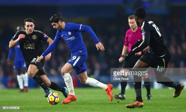 Alvaro Morata of Chelsea runs with the ball under pressure from Matty James and Daniel Amartey of Leicester City during the Premier League match...
