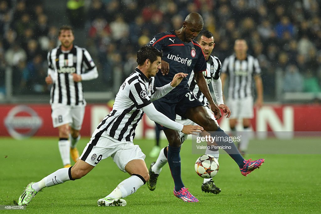 Alvaro Morata (L) of Juventus clashes with Eric Abidal of Olympiacos FC during the UEFA Champions League group A match between Juventus and Olympiacos FC at Juventus Arena on November 4, 2014 in Turin, Italy.