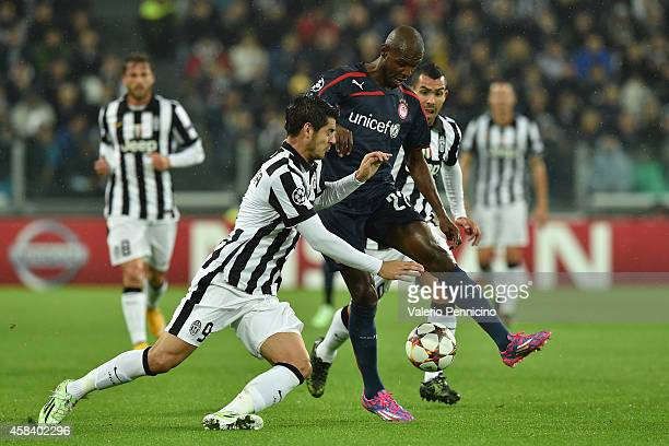 Alvaro Morata of Juventus clashes with Eric Abidal of Olympiacos FC during the UEFA Champions League group A match between Juventus and Olympiacos FC...