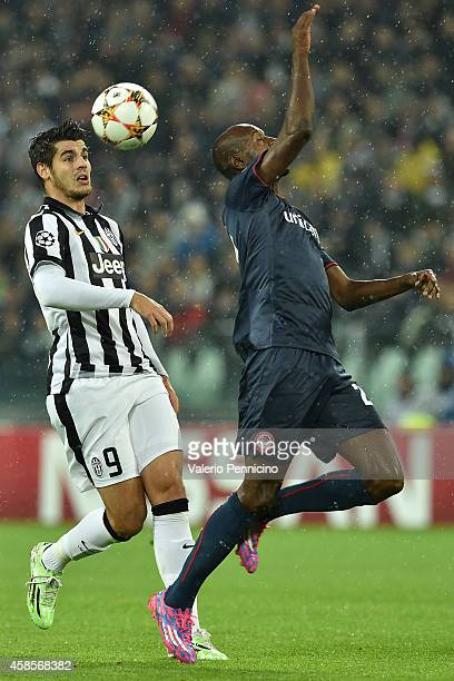 Alvaro Morata of Juventus is challenged by Eric Abidal of Olympiacos FC during the UEFA Champions League group A match between Juventus and...