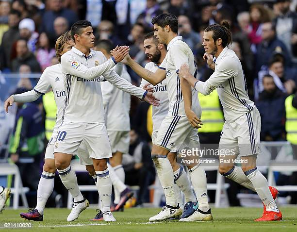 Alvaro Morata of Real Madrid celebrates with James Rodriguez after scoring their team's third goal during the La Liga match between Real Madrid CF...
