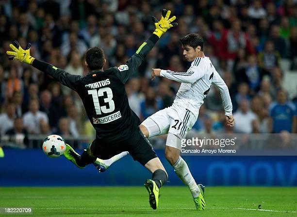 Alvaro Morata of Real Madrid CF strikes the ball past goalkeeper Thibaut Courtois of Atletico de Madrid during the La Liga match between Real Madrid...
