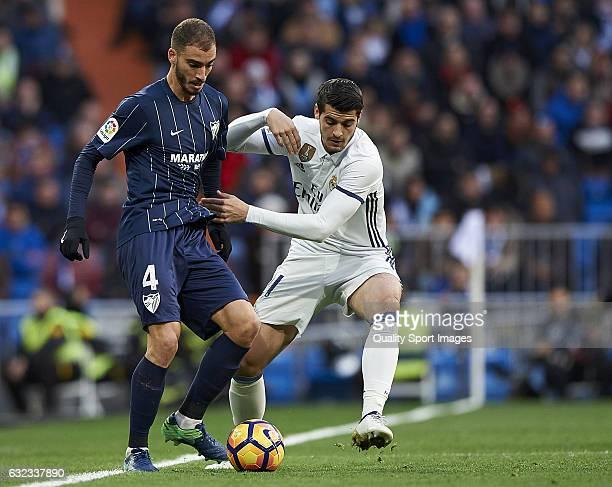 Alvaro Morata of Real Madrid competes for the ball with Mikel Villanueva of Malaga during the La Liga match between Real Madrid CF and Malaga CF at...