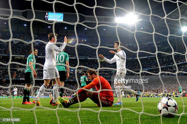 Alvaro Morata of Real Madrid is congratulated by teammate Gareth Bale after scoring his team's third goal whilst dejected goalkeeper Ralf Fahrmann of...