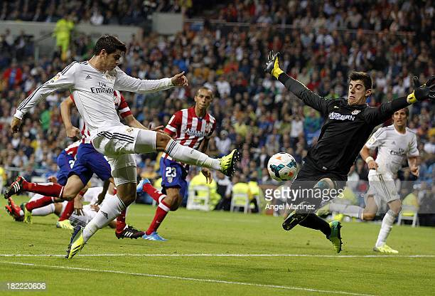 Alvaro Morata of Real Madrid shoots on goal past goalkeeper Thibaut Courtois of Atletico de Madrid during the La Liga match between Real Madrid and...