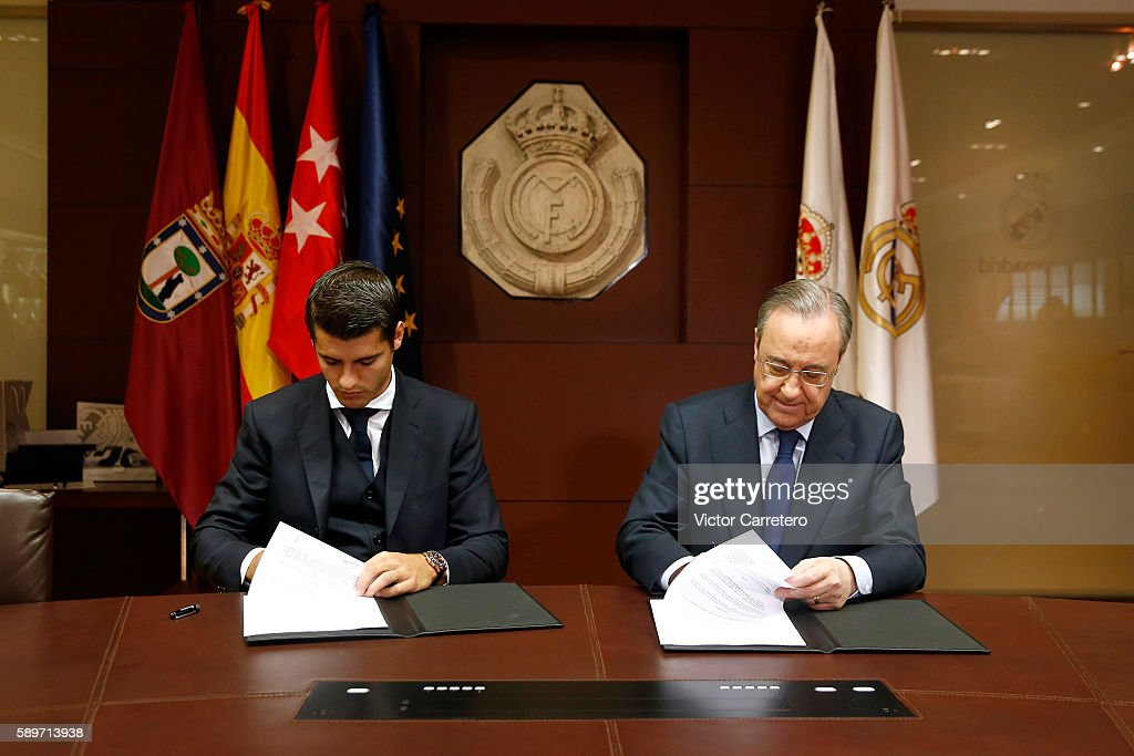 Alvaro Morata (L) of Real Madrid signs his contract beside Real Madrid president Florentino Perez during his official presentation at Estadio Santiago Bernabeu on August 15, 2016 in Madrid, Spain.