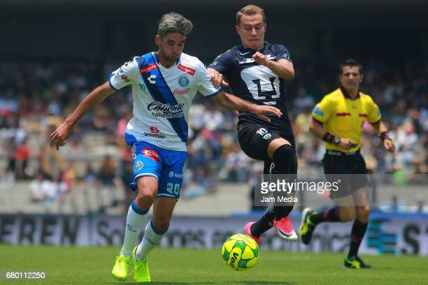 Alvaro Navarro of Puebla fights for the ball with Abraham Gonzalez of Pumas during the 17th round match between Pumas UNAM and Puebla as part of the...