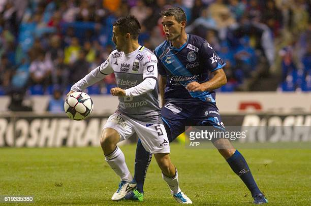 Alvaro Navarro of Puebla vies for the ball with Fernando Navarro of Leon during their Mexican Apertura 2016 Tournament football match at the...