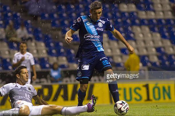 Alvaro Navarro of Puebla vies for the ball with Guillermo Burdisso of Leon during their Mexican Apertura 2016 Tournament football match at the...