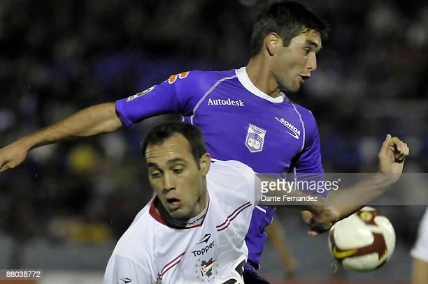 Alvaro Navarro of Uruguay's Defensor Sporting and Leandro Desabato of Argentina's Estudiantes de la Plata jump for the ball during their Santander...