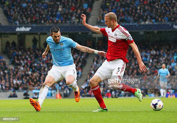 Alvaro Negredo of Manchester City and Brede Hangeland of Fulham compete for the ball during the Barclays Premier League match between Manchester City...