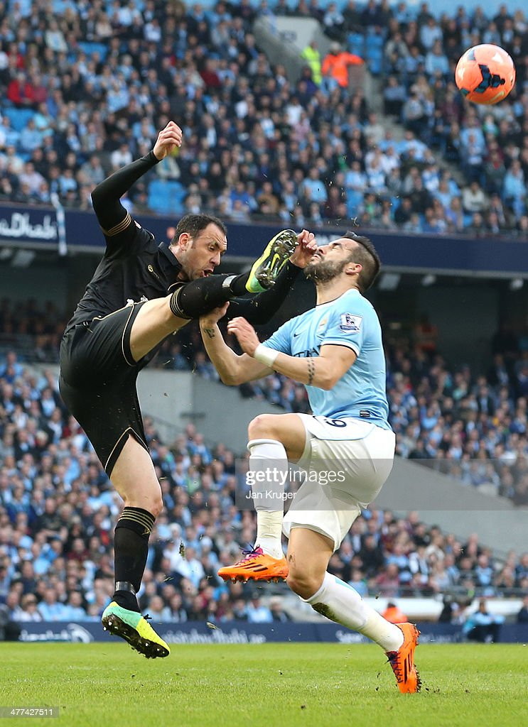Alvaro Negredo of Manchester City battles with Ivan Ramis of Wigan Athletic during the FA Cup Quarter-Final match between Manchester City and Wigan Athletic at the Etihad Stadium on March 9, 2014 in Manchester, England.