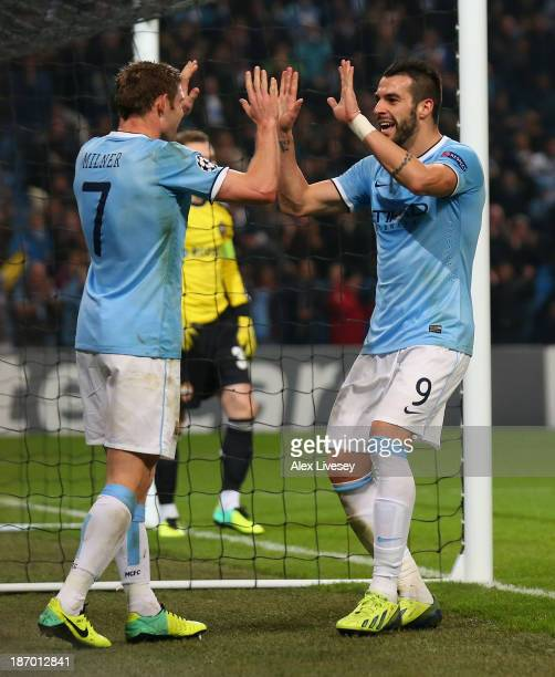 Alvaro Negredo of Manchester City celebrates with his teammate James Milner after scoring his team's fifth goal to complete his hattrick during the...