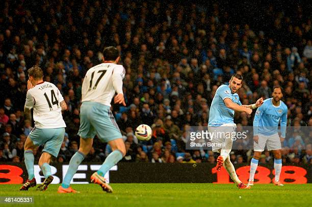 Alvaro Negredo of Manchester City scores their fourth goal and his hat trick goal during the Capital One Cup SemiFinal first leg match between...