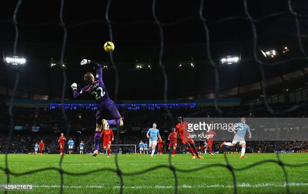 Alvaro Negredo of Manchester City shoots to score past Simon Mignolet of Liverpool during the Barclays Premier League match between Manchester City...