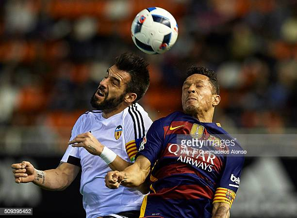 Alvaro Negredo of Valencia competes for the ball with Adriano of Barcelona during the Copa del Rey Semi Final second leg match between Valencia CF...