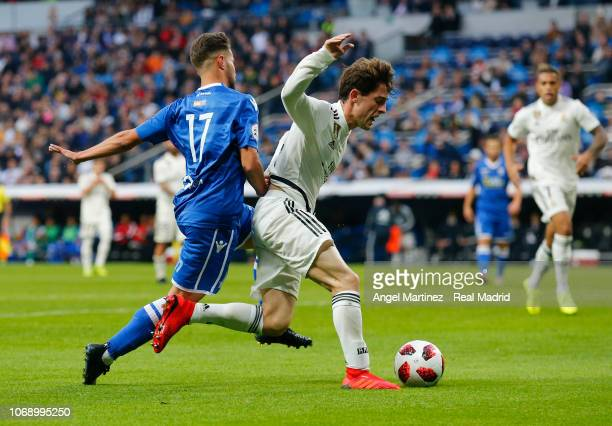 Alvaro Odriozola of Real Madrid competes for the ball with Braim Amar Romero of Melilla during the Copa del Rey fourth round second leg match between...