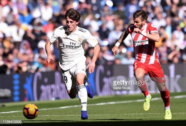 Alvaro Odriozola of Real Madrid is challenged by Portu of Girona during the La Liga match between Real Madrid CF and Girona FC at Estadio Santiago...