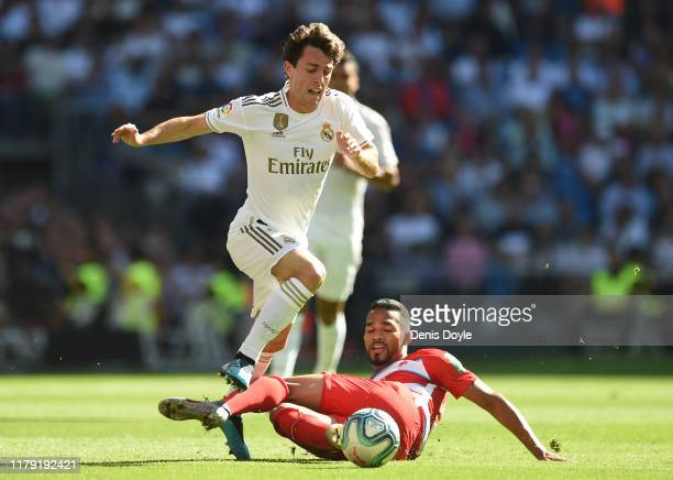 Alvaro Odriozola of Real Madrid is tackled by Domingos of Granada during the Liga match between Real Madrid CF and Granada CF at Estadio Santiago...