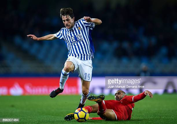 Alvaro Odriozola of Real Sociedad competes for the ball with Guido Pizarro of Sevilla FC during the La Liga match between Real Sociedad and Sevilla...