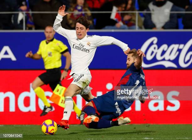 Alvaro Odrizola of Real Madrid competes for the ball with Jorge Pulido of SD Huesca during the La Liga match between SD Huesca and Real Madrid CF at...