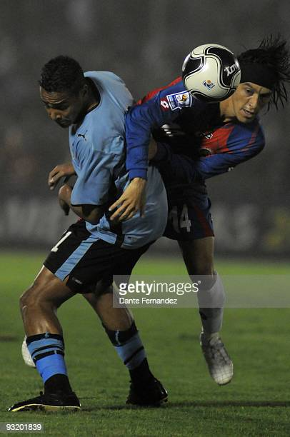 Alvaro Pereira of Uruguay vies for the ball with Bolanos Navarro of Costa Rica during their match as part of the 2010 World Cup Qualifiers at the...